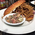 Barbecue pulled pork sandwich with crispy onions, coleslaw, and potato salad