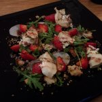 Grilled goat cheese with strawberries, arugula, white radish, seed praline, and pomegranate sauc