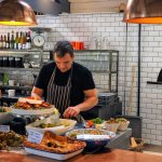salads and other dishes on offer with pizzas about to go in pizza oven