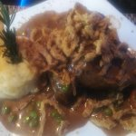 Meat loaf with mashed potatoes and gravey with peas and carrots topped with string fried onion.