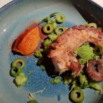 Grilled octopus, served over herbed root vegetables and olives, with an anchovy mousse.