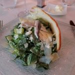 Caesar salad with bread partial shell and single anchovy laid across the top.