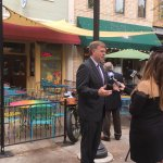 The mayor makes a TV appearance in front of the restaurant.