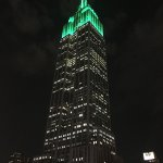 View of the Empire State Building from the roof of Hotel Metro with green flood lights.