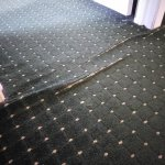 Carpeting lifting from floor entrance into second bedroom