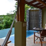 infinity plunge pool with rock wall waterfall, plenty of seating, loungers and a hammock