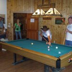 Gather around the pool table and play and watch a sport event on the flat screen at the same tim