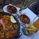 Delicious seafood paella, sausage, olives, and fries.