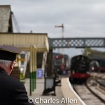 The uniformed stationmaster waits for the train to arrive at Embsay