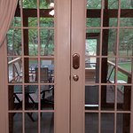 French doors off living room leading to screened in hot tub porch and outdoor deck