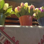 Tulips in ceramic pots and an embroidered handicraft makes the interior homey