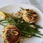 Crab cakes served with wild rice and fresh string beans.