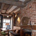The old brick chimney breast and ceiling beams taken back to their original colour and NOT paint