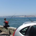 De straat uit en naar links zie je diverse vissers. Aan de overkant zie je Lissabon.