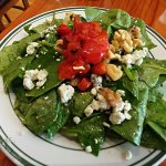 Half spinach salad with pesto, walnuts, gorgonzola and peppers
