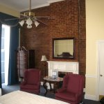 Exposed brick wall and high ceilings in our room