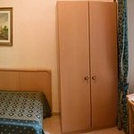 Single (twin) bed, armoire, and desk. Note key plate inserted into light switch fixture.