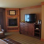 Gas Fireplace and large TV. Dresser with microwave and mini fridge behind large door. Coffee mak