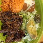 Carnitas- Michoacan style pork served with jalapenos, lettuce, avocado, rice, refried beans