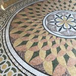 Small tiles inlaid through out marble floors.