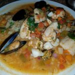Pescado a la Gloria with tilapia, shrimp, scallops, red snapper & mussels on rice & in broth