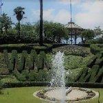Zona centrale con fontana, lago dei cigni e orologio verde.