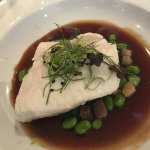 Poached pavé of wild Atlantic halibut with buttered fèves, lardons and red wine sauce