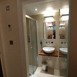 View into the bathroom; there are not two sinks. It is the reflection in the back of the glass d