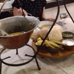 The soup is served in a cauldron, with garlic dressing, hot peppers, and bread.