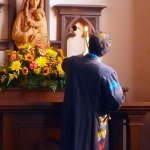 Acolyte lighting a candle at the Mary altar.
