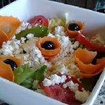 Insalata con lattuga, pomodori, carote, mais, olive nere e feta greca