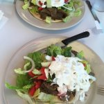 Tzikii sauce over fresh lettuce, tomatoes and onions on top of delicious gyro meat on fresh pita