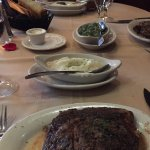 Prime ribeye steak with mashed potatoes and creamed spinach sides.