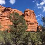 Amazing red rock formations, towering over ancient ruins.