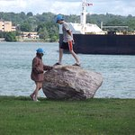 Children playing while freighter passes by. Canada is in the background.