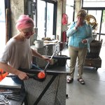 Blowing molten glass into a wine glass.