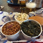 Barbecue Sandwich with sides of beans and greens.
