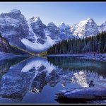 As the sun rises over Moraine Lake, the colors and shadows and air all begin to move and change.