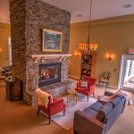 Reception room with double sided stone fireplace and views of the gardens and waterfall