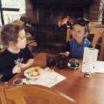 Kids sitting in front of fire enjoying fluffys and colouring in