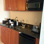Kitchenette with microwave, refrigerator, sink and Illy coffee machine.
