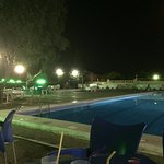 Pool area at night, enjoy drinks outside and still hear the singers