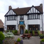 Attractive pub frontage with planted containers and outdoor seating