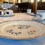 Aan tafel gereserveerd ontbijt met mooi tafel linnen en servies.