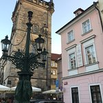"""Hotel entrance right at the end of Charles Bridge with """"standard room """" photos in the building a"""