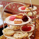 Afternoon tea with tasty sandwiches, fresh scone with cream and jam and quality macaroons