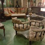 """""""conversation chair"""" in sitting room, many interesting photos on walls"""