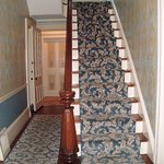This staircase leads to the guest rooms, and it has a carpet runner on it.