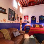 The Patzcuaro Suite Den with Queen bed and leather love-seat. Room opens from Courtyard.