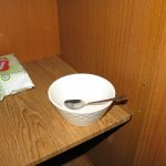 Dirty bowl in cupboard accompanied by packet of 'Pampers' and the bible.